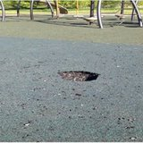 Hole gouged out of new resilient matting under play equipment
