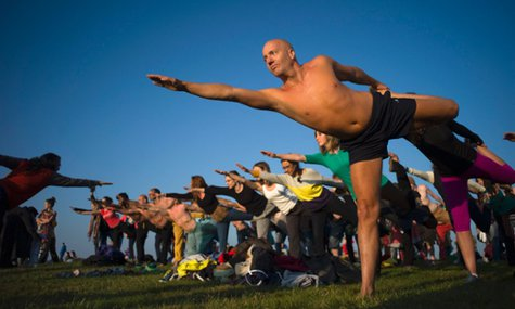 Stonehenge summer solstice 2014 Visitors gather for some yoga to greet the sun at Stonlamber for the best vantage point … Photograph: Kieran Doherty/Reuters
