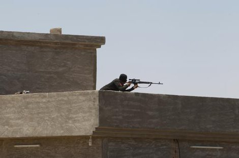 A member of the Iraqi security forces aims his rifle as he takes up position during an intensive security deployment west of Baghdad, June 24, 2014.  CREDIT: REUTERS/AHMED SAAD