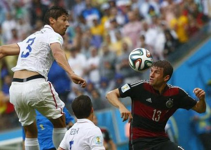 Omar Gonzalez of the U.S.(3) jumps for the ball with Germany's Thomas Mueller (R) during their 2014 World Cup Group G soccer match at the Pernambuco arena in Recife June 26, 2014. CREDIT: REUTERS/TONY GENTILE