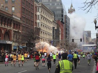 Runners continue to run towards the finish line of the Boston Marathon as an explosion erupts near the finish line of the race in this photo exclusively licensed to Reuters by photographer Dan Lampariello after he took the photo in Boston, Massachusetts, April 15, 2013. CREDIT: REUTERS/DAN LAMPARIELLO
