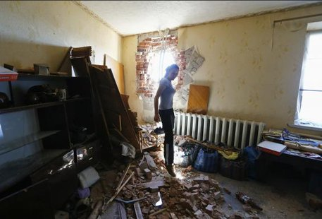 Local resident Tatyana Markova walks inside a house damaged by shelling in the Ukrainian eastern city of Slaviansk July 1, 2014. REUTERS/Shamil Zhumatov