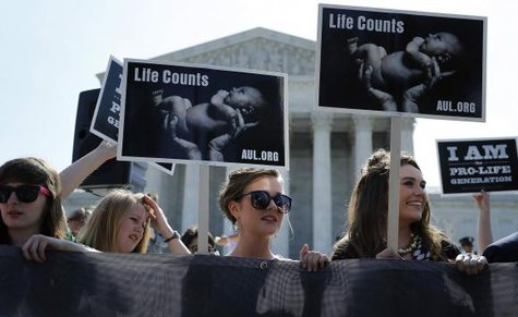 Anti-abortion demonstrators wait for the U.S. Supreme Court ruling in the Hobby Lobby case to be announced in Washington June 30, 2014. CREDIT: REUTERS/JONATHAN ERNST