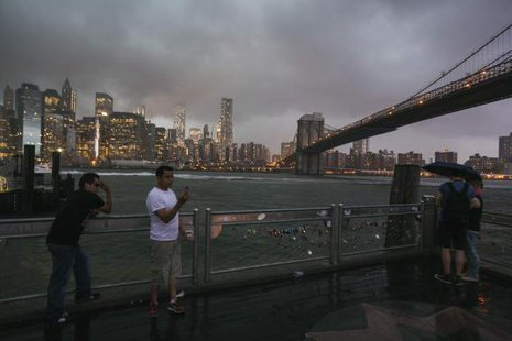 Tourists stand underneath the Brooklyn Bridge to photograph a summer storm bearing down on New York July 2, 2014.  CREDIT: REUTERS/LUCAS JACKSON