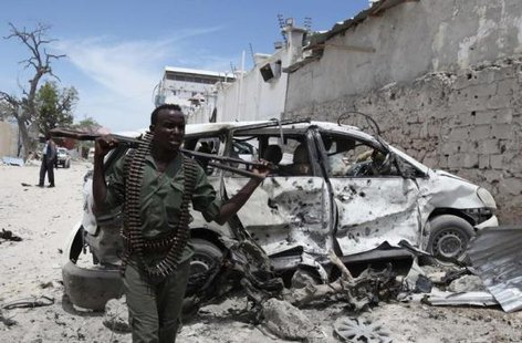 A Somali government soldier walks next to a car damaged in an explosion near Al Mukaram Hotel in Mogadishu March 15, 2014. CREDIT: REUTERS/OMAR FARUK