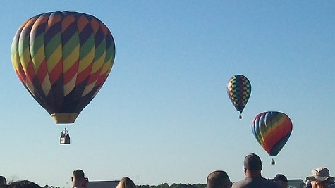 Hot Air balloons maneuver over Kellogg Field aiming for two big markers on the ground.