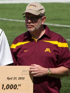 University President Eric W. Kaler, receiving a scholarship donation check at the Minnesota Golden Gophers football team's 2013 Spring Game in TCF Bank Stadium, Minneapolis, Minnesota, USA. By Bobak Ha'Eri (Own work) [CC-BY-3.0 (http://creativecommons.org/licenses/by/3.0)], via Wikimedia Commons