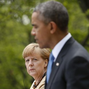 German Chancellor Angela Merkel listens to President Barack Obama address a joint news conference in the Rose Garden of the White House in Washington. REUTERS/Kevin Lamarque