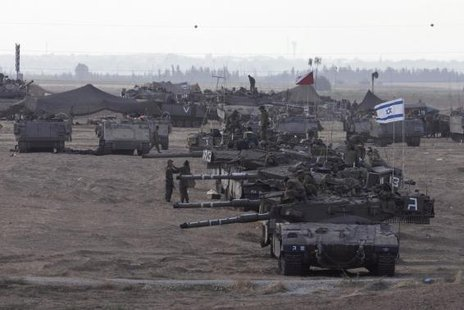 Israeli tanks and armoured personnel carriers (APCs) are seen at a staging area outside the central Gaza Strip July 15, 2014. Credit: Reuters/Baz Ratner