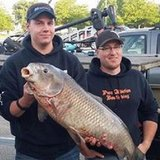 Josh Teunis with fishing buddy Bill Kimball on the right and his record catch.  (photo courtesy DNR).