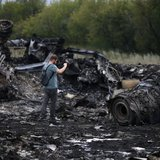 A journalist takes photographs at the site of Thursday's Malaysia Airlines Boeing 777 plane crash near the settlement of Grabovo, in the Donetsk region July 18, 2014.  REUTERS/Maxim Zmeyev