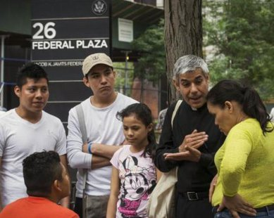 Father Fabian Arias, (2nd R) an advocate with the New Sanctuary Coalition of New York City, an immigration advocacy group, speaks with immigrants following their immigration hearings at the U.S. Federal Building in New York, in this July 10, 2014 file photo. REUTERS/Brendan McDermid
