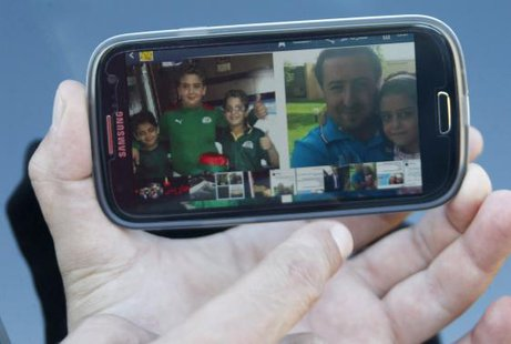 A relative of Lebanese national Manji Hasan holds up his mobile phone displaying a picture of Manji and his children, who the family said were all on board Air Algerie flight AH 5017, in the southern Lebanese village of Hariss July 24, 2014. REUTERS/Ali Hashisho