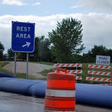 Interstate highway rest area sign. (Photo By Bri Weldon (Flooded Road  Uploaded by xnatedawgx) [CC-BY-2.0 (http://creativecommons.org/licenses/by/2.0)], via Wikimedia Commons).