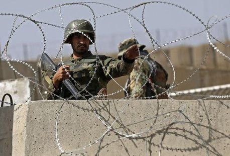 An Afghan National Army (ANA) soldier keeps watch at the gate of a British-run military training academy Camp Qargha, in Kabul August 5, 2014.  CREDIT: REUTERS/OMAR SOBHANI