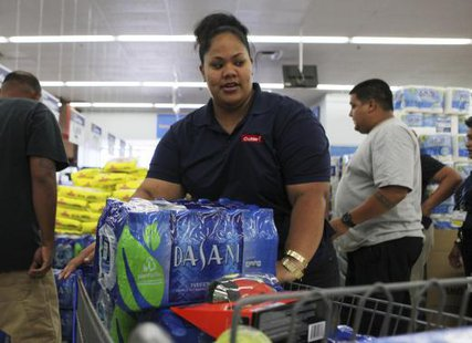 Andrea Malosa loads bottled water into her shopping cart while buying supplies as a hurricane and a tropical storm approach the Hawaiian islands, in Mililani, Hawaii, August 5, 2014. CREDIT: REUTERS/HUGH GENTRY