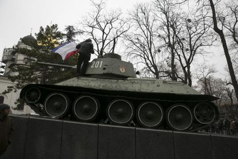 A man holds the Crimea flag on top of an old Soviet tank during rallies near the Crimean parliament building in Simferopol February 26, 2014.  CREDIT: REUTERS/BAZ RATNER