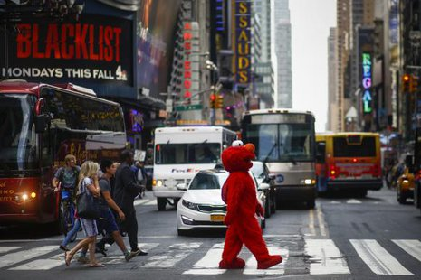 Jorge, an immigrant from Mexico, walks across an intersection dressed as the Sesame Street character Elmo, in Times Square, New York July 30, 2014. CREDIT: REUTERS/EDUARDO MUNOZ