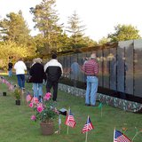 Visitors experience the Vietnam Moving Wall. The traveling wall, a one-half size replica of the Vietnam Veterans Memorial in Washington, D.C. (Photo By U.S. Navy photo by Mass Communication Specialist 1st Class Barbara L. Bailey [Public domain], via Wikimedia Commons).