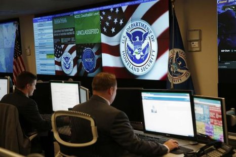 U.S. Department of Homeland Security employees work in front of U.S. threat level displays inside the National Cybersecurity and Communications Integration Center during a guided media tour in Arlington, Virginia June 26, 2014. CREDIT: REUTERS/KEVIN LAMARQUE