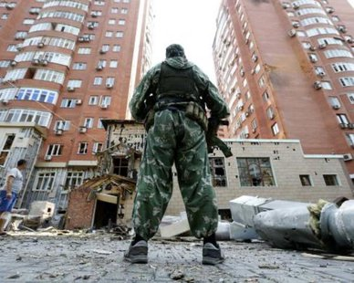 An armed pro-Russian separatist stands in front of damaged buildings following what locals say was shelling by Ukrainian forces in Donetsk August 7, 2014. REUTERS/Sergei Karpukhin