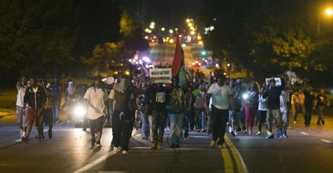 Demonstrators march in the street while protesting the shooting death of black teenager Michael Brown in Ferguson, Missouri August 12, 2014.  CREDIT: REUTERS/MARIO ANZUONI