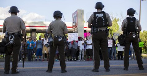 Police officers watch as demonstrators protest the death of black teenager Michael Brown in Ferguson, Missouri August 12, 2014. Police said Brown, 18, was shot in a struggle with a gun in a police car but have not said why Brown was in the car.  REUTERS/Mario Anzuoni