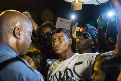 Missouri State Highway Patrol Captain Ron Johnson (L) speaks to protesters as he walks through a peaceful demonstration as communities continue to react to the shooting of Michael Brown in Ferguson, More... CREDIT: REUTERS/LUCAS JACKSON