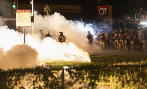 Riot police clear a street with smoke bombs while clashing with demonstrators in Ferguson, Missouri August 13, 2014.  CREDIT: REUTERS/MARIO ANZUONI