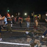 Protesters throw rocks and attempt to block the street after protests in reaction to the shooting of Michael Brown turned violent near Ferguson, Missouri August 17, 2014.  CREDIT: REUTERS/LUCAS JACKSON