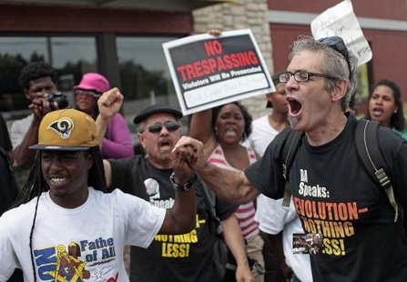 Demonstrators protesting Michael Brown's murder yell at police in Ferguson, Missouri August 18, 2014.  CREDIT: REUTERS/JOSHUA LOTT