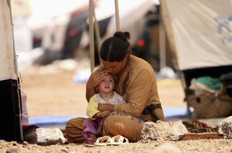 A refugee woman from the minority Yazidi sect, who fled the violence in the Iraqi town of Sinjar, sits with a child inside a tent at Nowruz refugee camp in Qamishli, northeastern Syria August 17, 2014. CREDIT: REUTERS/RODI SAID