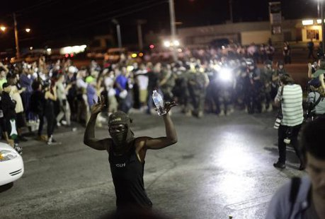 A demonstrator raises his arms during a protest against the shooting of Michael Brown as police in riot gear watch in Ferguson, Missouri August 19, 2014.  CREDIT: REUTERS/JOSHUA LOTT