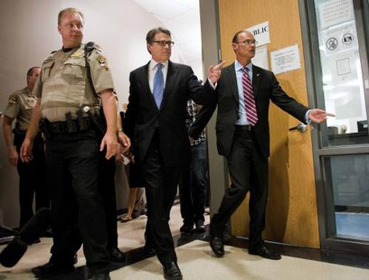 Texas Governor Rick Perry (C) enters the booking area at the Travis County courthouse in Austin, Texas August 19, 2014.  CREDIT: REUTERS/ASHLEY LANDIS