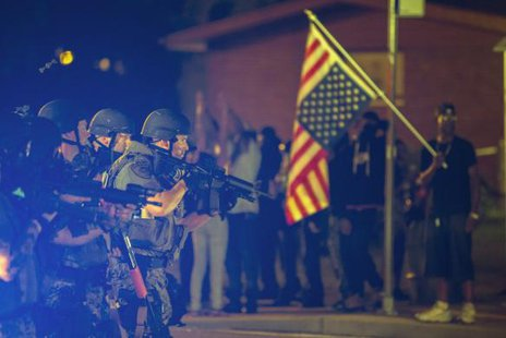 A police officer raises his weapon at a car speeding in his general direction as a more vocal and confrontational group of demonstrators stands on the sidewalk near Ferguson, Missouri August 18, 2014.  REUTERS/Lucas Jackson
