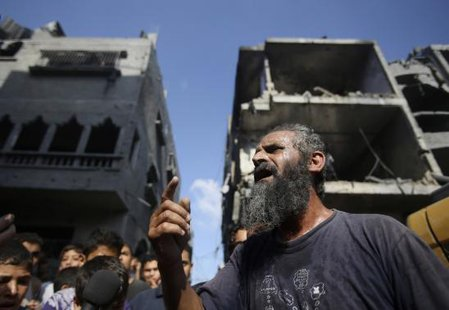 A Palestinian man reacts as rescue workers search for victims under the rubble of a house, which witnesses said was destroyed in an Israeli air strike that killed three senior Hamas military More... CREDIT: REUTERS/IBRAHEEM ABU MUSTAFA