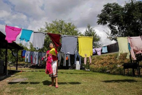 Crystal Ibarra, 23, reaches for her laundry in her backyard, which faces the border fence at the United States-Mexico border outside of Brownsville, Texas, August 5, 2014.  CREDIT: REUTERS/SHANNON STAPLETON
