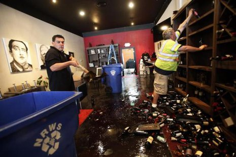 Rick Ruiz (L) and Tyler Paradise gather broken wine bottles from the floor of their Cult Following Wine Bar after an earthquake in Napa, California August 24, 2014.  CREDIT: REUTERS/STEPHEN LAM