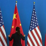 A Chinese woman adjusts a Chinese national flag next to U.S. national flags before a Strategic Dialogue expanded meeting, part of the U.S.-China Strategic and Economic Dialogue (S&ED) held at the Diaoyutai State Guesthouse in Beijing, July 10, 2014. CREDIT: REUTERS/NG HAN GUAN/POOL