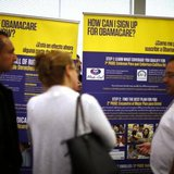 Julian Gomez (R) explains Obamacare to people at a health insurance enrolment event in Commerce, California March 31, 2014. CREDIT: REUTERS/LUCY NICHOLSON