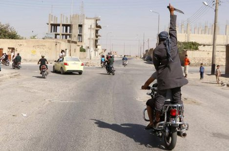 A man holds up a knife as he rides on the back of a motorcycle touring the streets of Tabqa city with others in celebration after Islamic State militants took over Tabqa air base, in nearby Raqqa city August 24, 2014. CREDIT: REUTERS/STRINGER