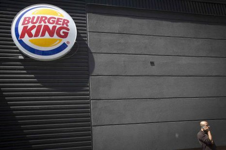A man talks on his phone underneath a Burger King logo outside the restaurant in the Brooklyn borough of New York August 25, 2014. CREDIT: REUTERS/CARLO ALLEGRI
