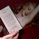 An employee of Butterfields auction house displays a copy of a model release signed by Marilyn Monore in front of one of the photographs of Monroe during a Hollywood photo shoot in 1949, in Los Angeles, March 22, 2001. A 15-minute film of Marilyn Monroe engaging in an oral sex act with an unidentified man will be kept from public view by a New York businessman who has bought it for $1.5 million, the broker of the deal said on Monday. REUTERS/Fred Prouser