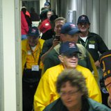 Veterans in yellow jackets disembark from the plane at Central Wisconsin Airport after taking their honor Flight (photo: Raymond Neupert - WSAU)