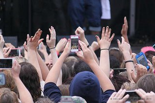 Person in a crowd taking a photo with their smartphone.
