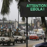 A U.N. convoy of soldiers passes a screen displaying a message on Ebola on a street in Abidjan August 14, 2014.  CREDIT: REUTERS/LUC GNAGO