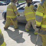 Students use pry bars to get door on wrecked car open.