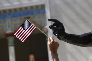 A girl holds a U.S. flag next to a sculpture after a naturalization ceremony at The Metropolitan Museum of Art in New York July 22, 2014. CREDIT: REUTERS/SHANNON STAPLETON