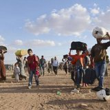 Syrian Kurds walk with their belongings after crossing into Turkey at the Turkish-Syrian border, near the southeastern town of Suruc in Sanliurfa province, September 20, 2014. Credit: Reuters/Stringer