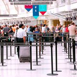 Passengers lining up at check-in counter at a modern international airport. Credit: Elena Elisseeva / Shutterstock.com